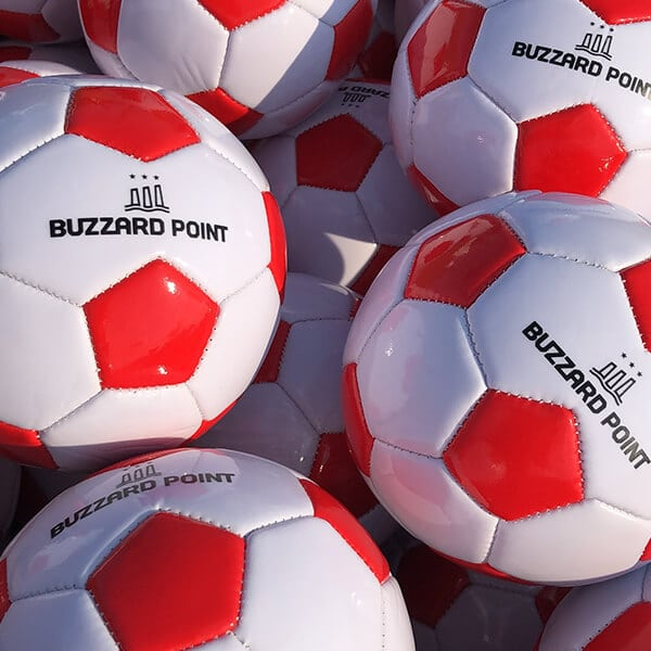 White and red soccer balls with Buzzard Point logo on them
