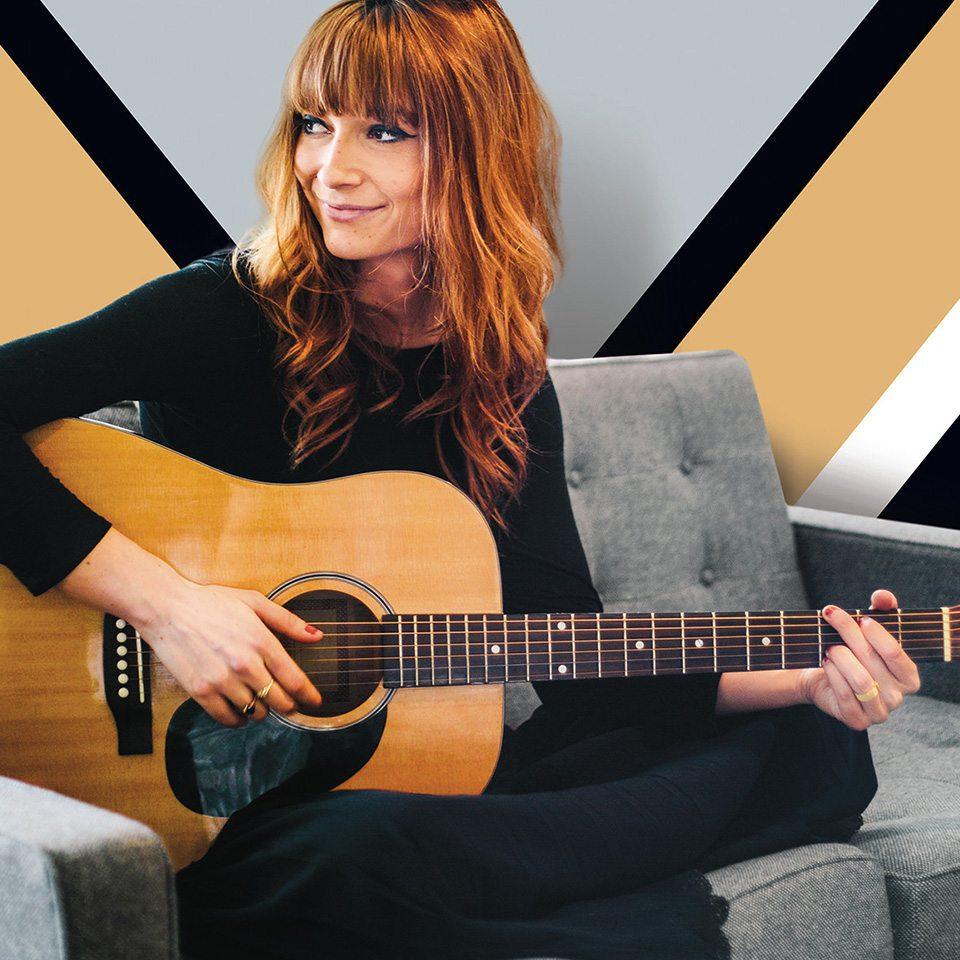 Woman with a guitar embodies Bozzuto's brand identity for their new apartment building branding efforts executed by top branding agency, Grafik.