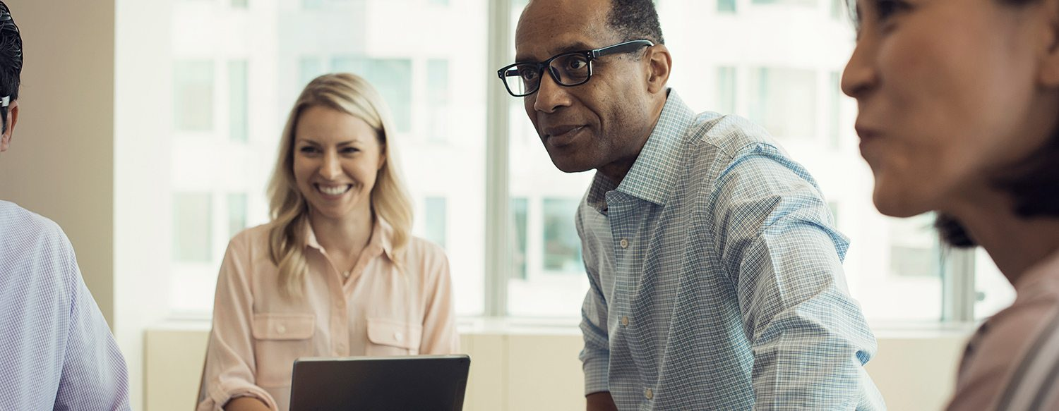 Image of 3 employees having a conversation