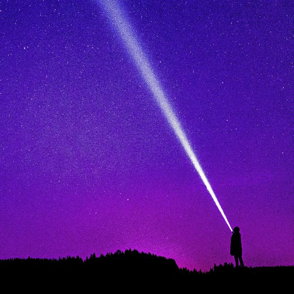person pointing flashlight at dark purple and blue sky