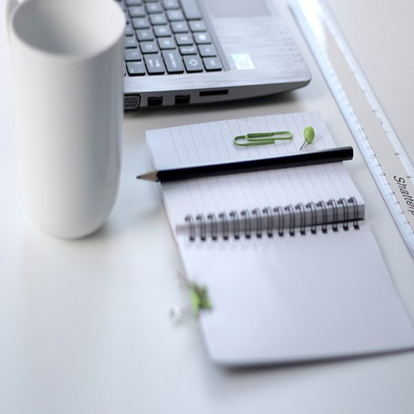 Pencil, notebook, laptop, and coffee mug on a desk
